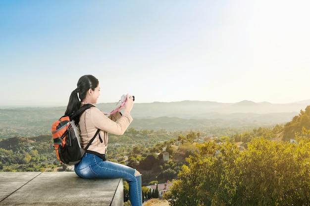 Donna asiatica con uno zaino seduto sul tetto e in possesso di una macchina fotografica per scattare foto