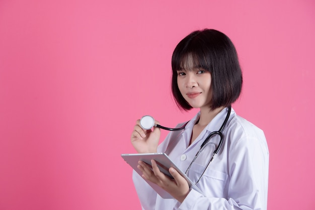 Donna asiatica del medico con il camice bianco sopra il rosa