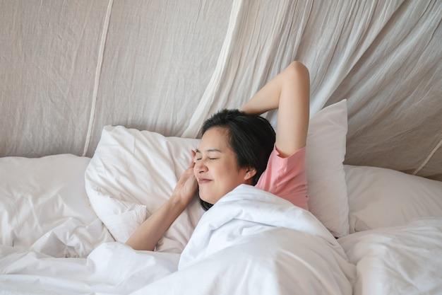 Donna asiatica del primo piano allungata dopo avere svegliato di mattina