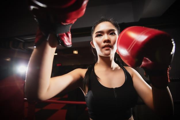 Donna asiatica del primo piano che fa esercizio di pugilato alla palestra