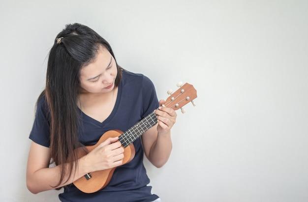 Donna asiatica del primo piano che gioca ukulele
