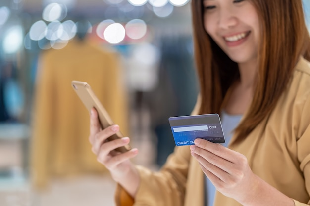 Donna asiatica del primo piano che usando la carta di credito con il cellulare per acquisto online nel grande magazzino