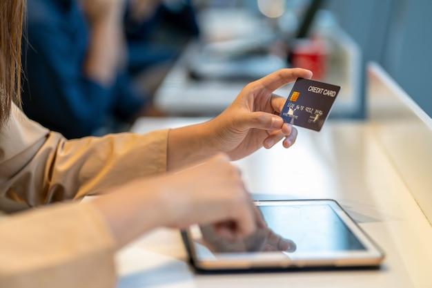 Donna asiatica del primo piano che usando la carta di credito con la compressa per acquisto online nel grande magazzino