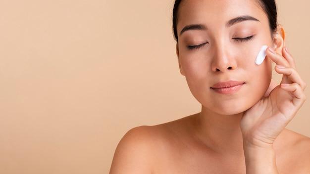 Donna asiatica del primo piano che usando la crema di fronte