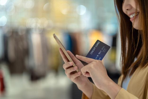 Donna asiatica del primo piano che utilizza la carta di credito con il cellulare per acquisto online nel grande magazzino