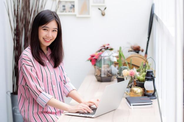 Donna asiatica del ritratto che lavora al computer portatile