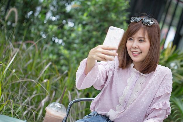 Donna asiatica del ritratto che prende selfie in caffetteria