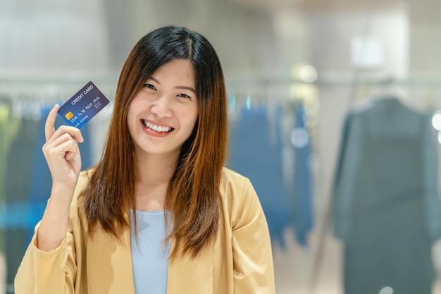 Donna asiatica del ritratto che tiene e che presenta la carta di credito per l'acquisto online nel grande magazzino