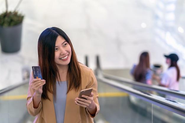 Donna asiatica del ritratto che usando la carta di credito con il telefono cellulare astuto per acquisto online nel dipartimento