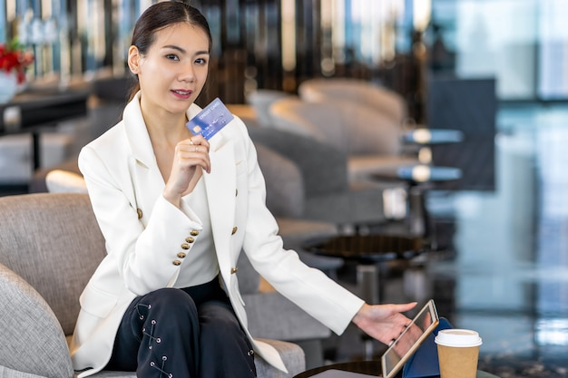 Donna asiatica del ritratto che usando la carta di credito con la compressa di tecnologia per l'acquisto online