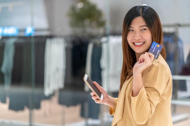 Donna asiatica del ritratto che utilizza la carta di credito con il telefono cellulare astuto per acquisto online nel grande magazzino