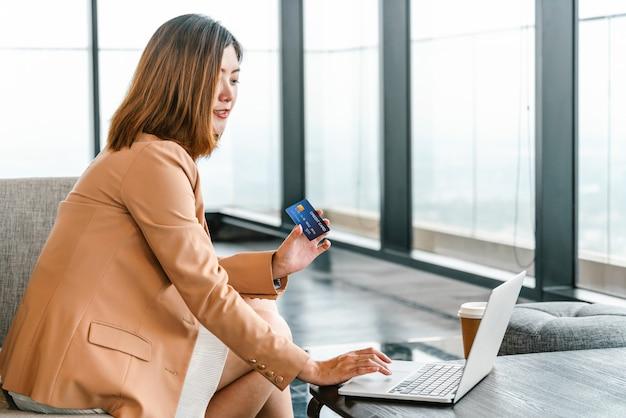Donna asiatica del ritratto che utilizza la carta di credito con il telefono cellulare, computer portatile per acquisto online nella hall moderna
