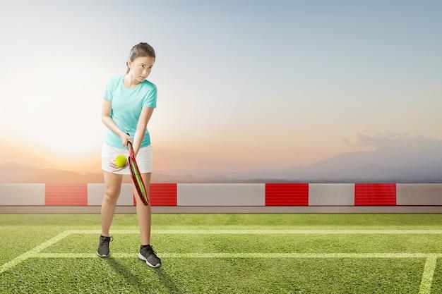 Donna asiatica del tennis con una racchetta e una palla di tennis in sue mani che servono la palla