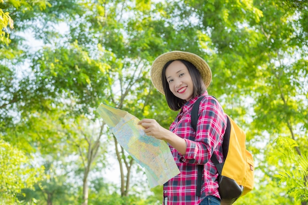 Donna asiatica del viaggiatore con lo zaino che cammina nella foresta tropicale, tenendo mappa e sorrisi