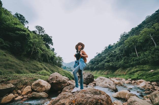 Donna asiatica del viaggiatore con lo zaino che si rilassa e che gode della vista del fiume della montagna