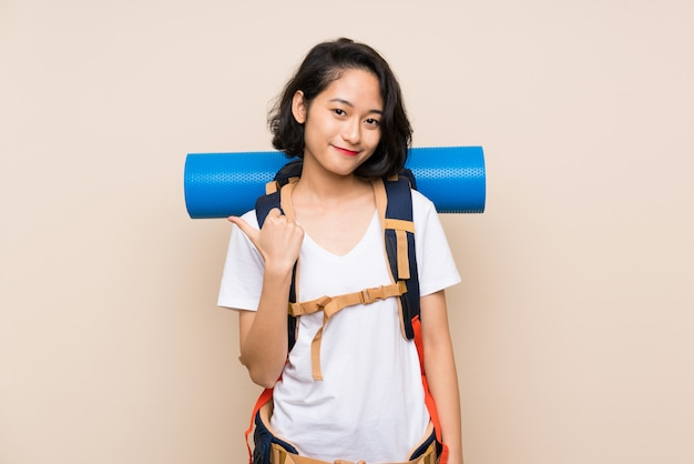 Donna asiatica del viaggiatore sopra isolato che indica il lato per presentare un prodotto