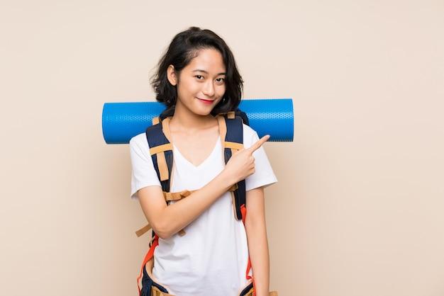 Donna asiatica del viaggiatore sopra la parete isolata che indica il lato per presentare un prodotto