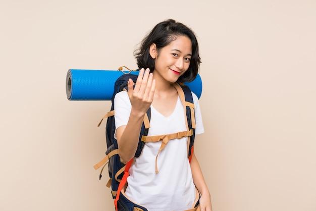 Donna asiatica del viaggiatore sopra la parete isolata che invita a venire con la mano, felice che tu sia venuto