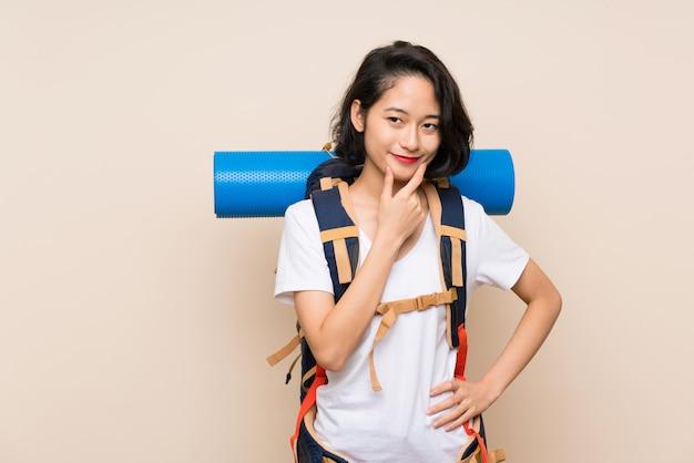Donna asiatica del viaggiatore sopra la parete isolata che pensa un'idea