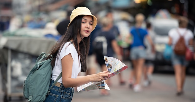 Donna asiatica del viaggiatore sul mercato di strada con la mappa, nella città di bangkok della tailandia.
