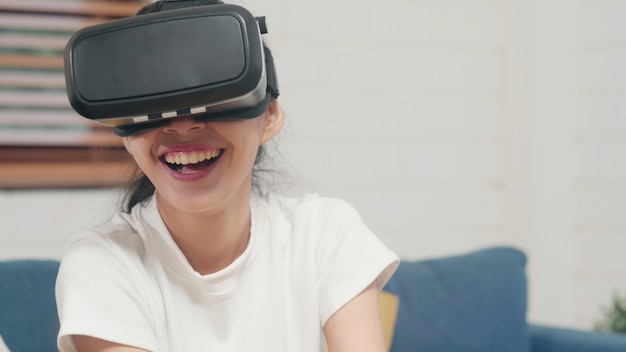 Donna asiatica dell'adolescente che utilizza il simulatore di realtà virtuale di vetro che gioca i video giochi in salone
