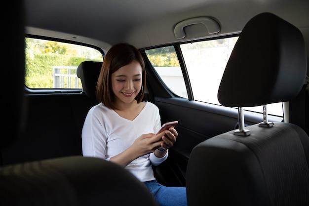 Donna asiatica dell'adolescente che utilizza uno smartphone nel sedile posteriore dell'auto, i passeggeri utilizzano un'app per ordinare un giro e condividere il concetto di condivisione peer-to-peer