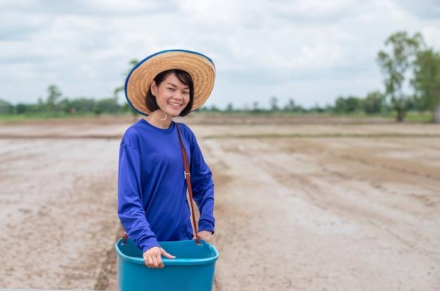 Donna asiatica dell'agricoltore che tiene la condizione blu del pucket e sorridere al campo dell'azienda agricola del riso