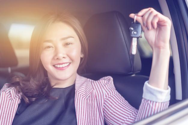 Donna asiatica dell'autista che sorride e che mostra nuova chiave dell'automobile mentre sedendosi in un'automobile