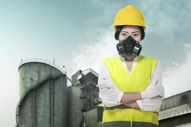 Donna asiatica dell'ingegnere di costruzione che usando una maschera protettiva per proteggerla dall'inquinamento atmosferico