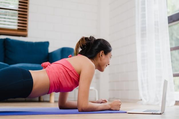 Donna asiatica dell'istruttore di yoga che per mezzo del computer portatile per l'insegnamento in tensione come fare yoga in salone a casa.