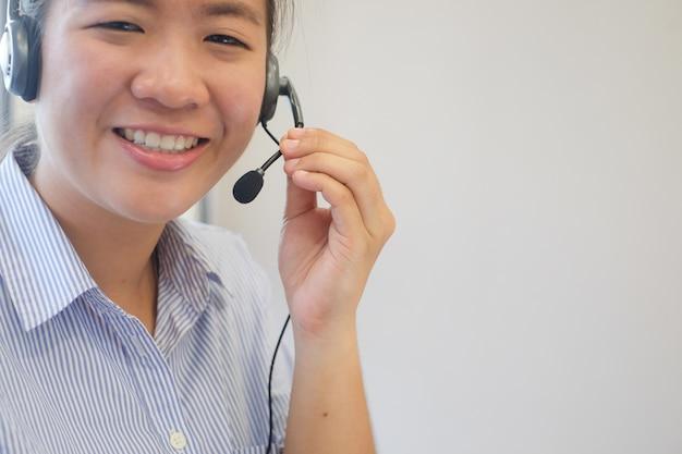 Donna asiatica della call center con la cuffia che prova alla risposta di risposta o al lavoro
