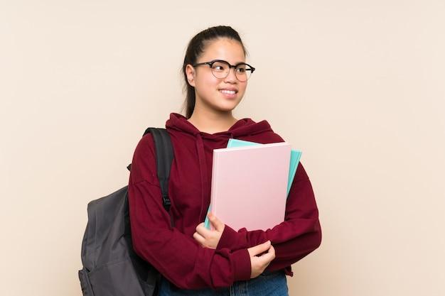 Donna asiatica della ragazza del giovane studente sopra la risata isolata del fondo