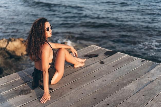 Donna asiatica della vaschetta graziosa che si distende sul pilastro vicino al mare in costume da bagno nero.