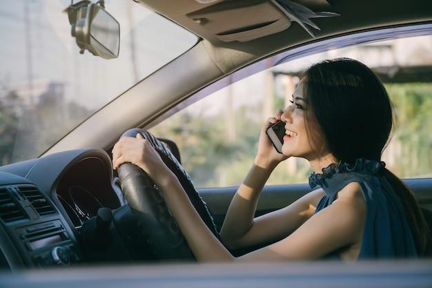 Donna asiatica di affari che parla al telefono mentre si viaggia in auto
