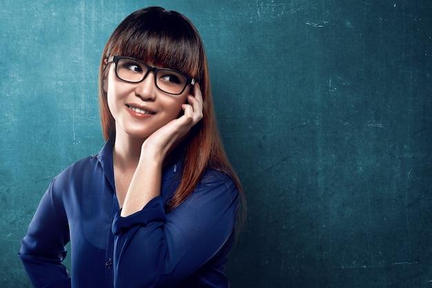 Donna asiatica di affari che parla tramite il suo cellulare