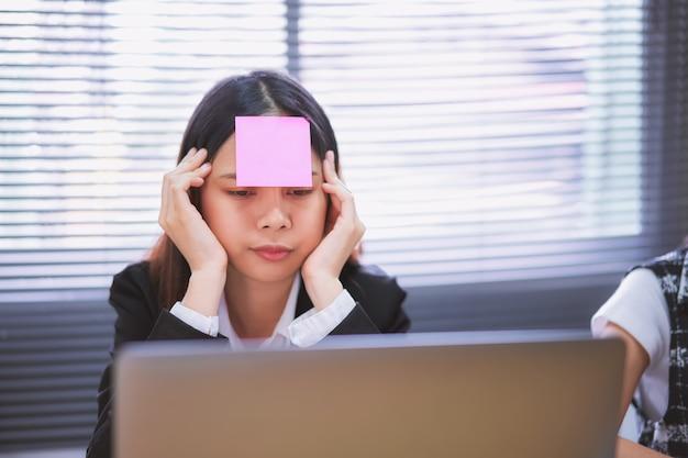 Donna asiatica di affari che si siede nell'ufficio e nel lavoro annoiato con il computer portatile.