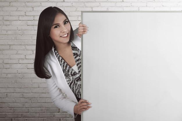 Donna asiatica di affari che tiene scheda in bianco