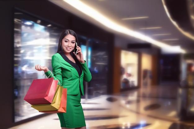 Donna asiatica di affari con i sacchetti della spesa che parla sul telefono