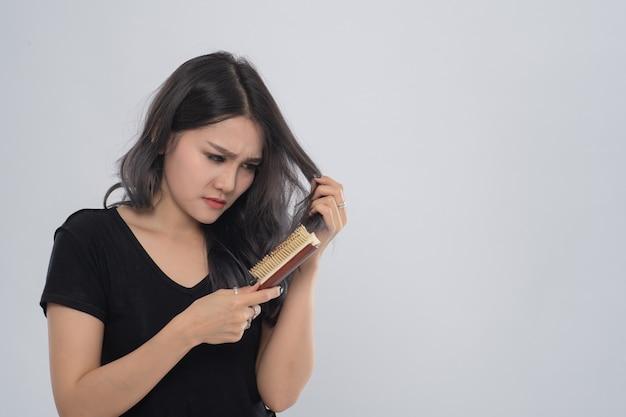 Donna asiatica di affari con un pettine e capelli problema su sfondo grigio