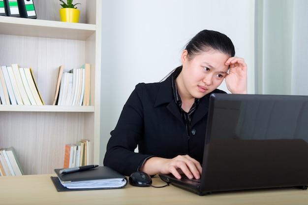 Donna asiatica di affari di emicrania che tiene la sua testa, funzionante con laktop
