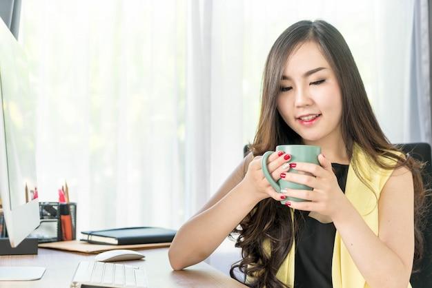 Donna asiatica di affari felice con la tazza di caffè