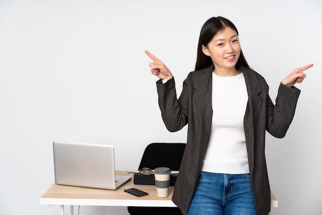 Donna asiatica di affari nel suo posto di lavoro sulla parete bianca che indica dito i laterali e felice