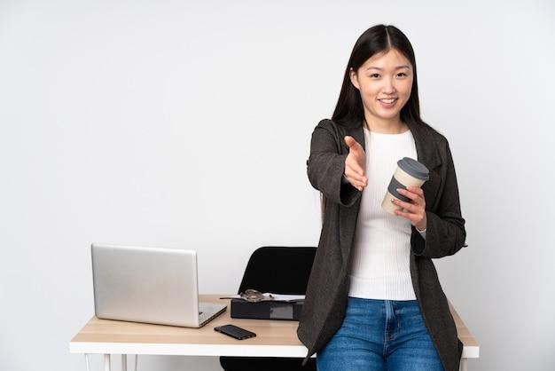 Donna asiatica di affari nel suo posto di lavoro sulla parete bianca che stringe le mani per chiudere molto