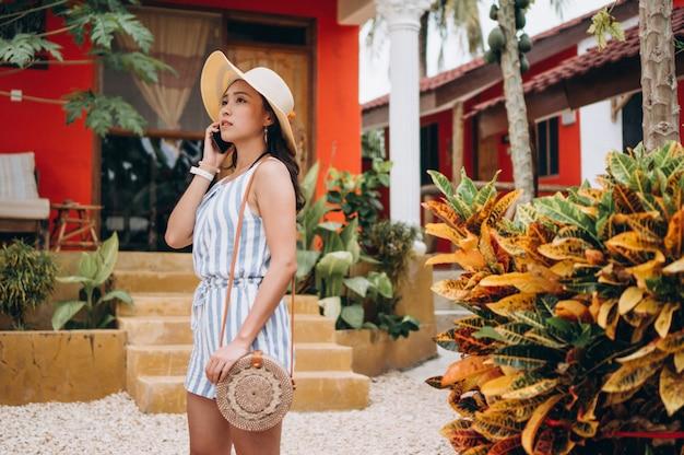 Donna asiatica di affari su una vacanza che parla sul telefono