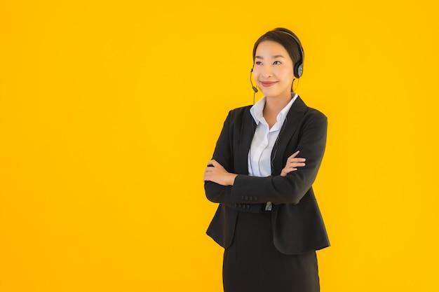 Donna asiatica di bei giovani affari del ritratto con la cuffia o la cuffia avricolare
