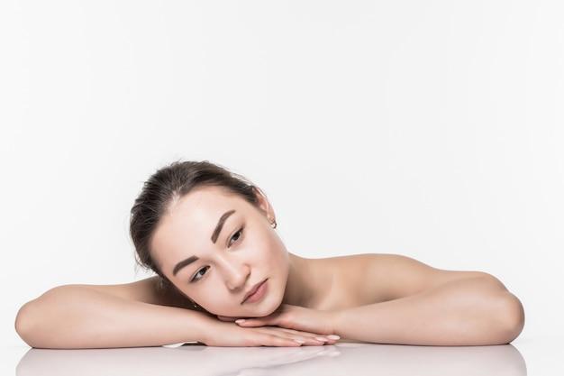 Donna asiatica di bellezza di bello skincare del fronte che si riposa con la riflessione di specchio isolata sulla parete bianca.