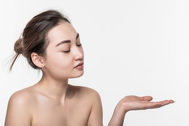 Donna asiatica di bellezza di cura dello skincare del corpo che mostra prodotto dal lato con la mano aperta che presenta e che mostra isolato sulla parete bianca.
