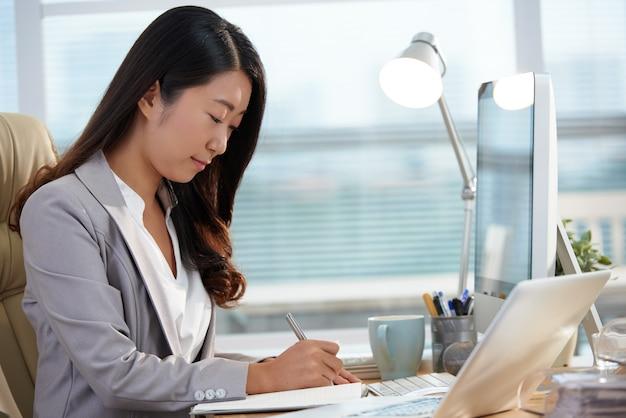 Donna asiatica di carriera che si siede allo scrittorio in ufficio e che lavora con i documenti