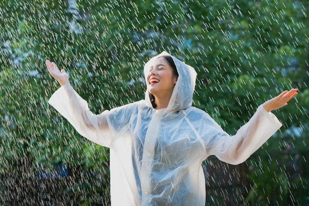 Donna asiatica di giorno piovoso che indossa un impermeabile all'aperto