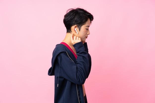 Donna asiatica di giovane sport sopra musica d'ascolto isolata della parete rosa